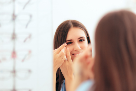Girl Trying on Medical Contact Lenses in the Mirror Stock Photo