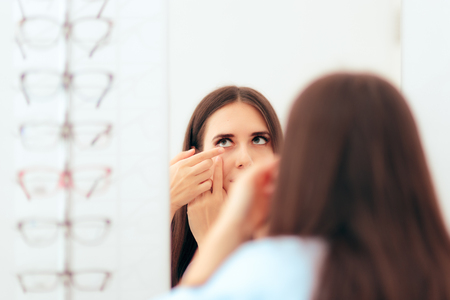 Girl Trying on Medical Contact Lenses in the Mirror