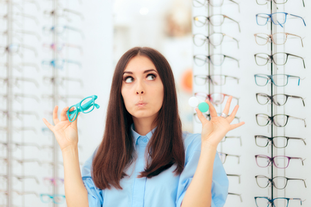 Woman Choosing Between Glasses and Contact Lenses in Optics Shop