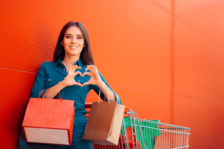 Girl with Shopping and Gift Bags in Front of a Supermarket Store Stock Photo