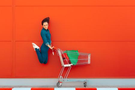 Mujer feliz con compras saltando de alegría Foto de archivo
