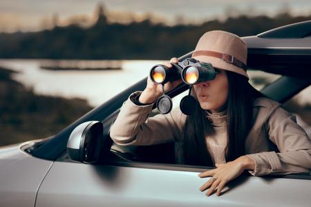 Detective femenino espiando con binoculares desde un coche Foto de archivo