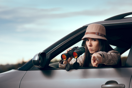 Female Detective Spying with Binocular from a Car Stock Photo