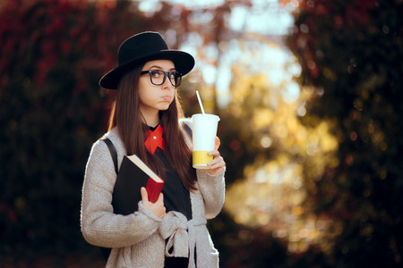 Hipster Student Holding a Book Outdoors in Autumn Decor