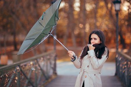 Ein Mädchen kämpft gegen den Wind und hält einen Regenschirm im Regen