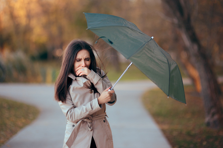 A girl fighting the wind holding an umbrella in the rain