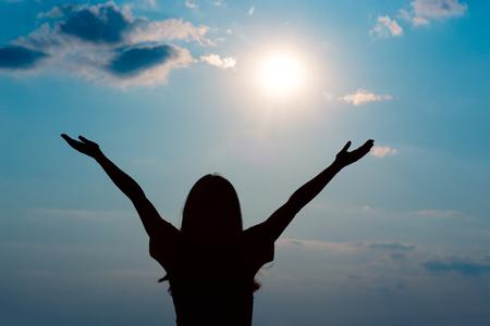 Una ragazza felice che alza le braccia guardando il sole