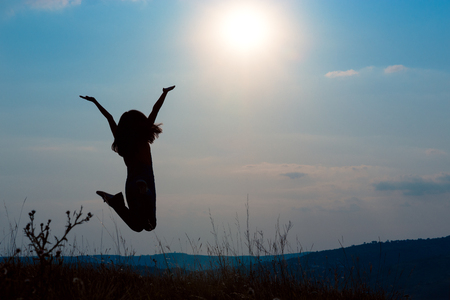 A happy girl raising her arms looking at the sun