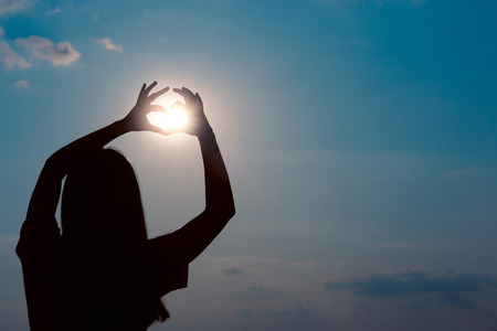 A woman making a heart sign gesture in sunset Banco de Imagens