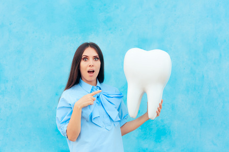 Funny Woman Holding Oversized Tooth in Dentist Concept Image Stock Photo