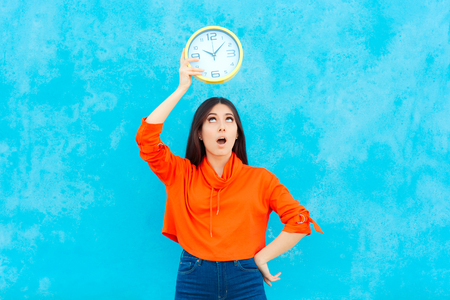 Woman Holding Clock Checking Time on Blue Background Stock Photo