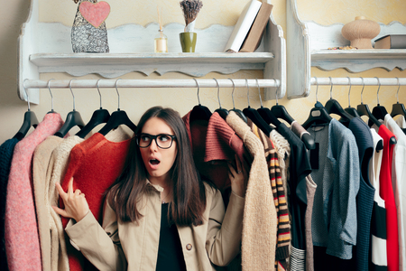 Funny Girl Between Many Sweaters on a Clothing Stander Archivio Fotografico