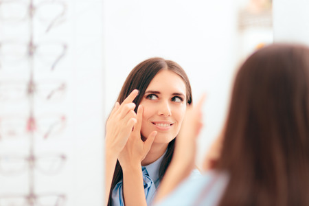Woman Putting on Medical Contact Lenses in the Mirror