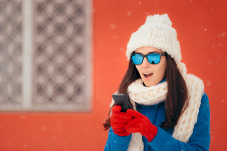 Surprised Winter Girl Checking Her Smartphone Stock fotó