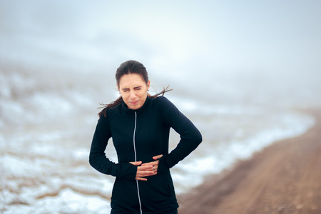 Woman Felling Pain While Running in Winter Cold