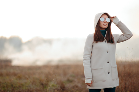 Fashion Girl with Cool Sunglasses Standing on a Field