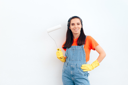 Woman Painting White Wall with Paint Roller Imagens
