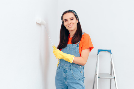 Woman Painting White Wall with Paint Roller Foto de archivo