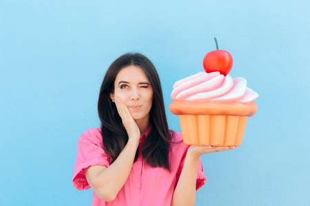 Woman Experiencing Tooth Ache from Eating Sweet Cupcake Imagens