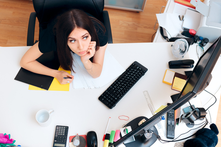 Tired Girl Sitting on Messy Desk Working Overtime Stock Photo
