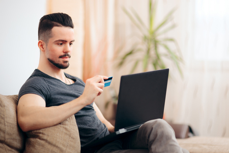 Man Holding Credit Card Shopping Online on His Laptop Stockfoto
