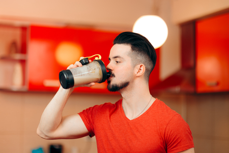Fit Healthy Man Drinking a Protein Shake in the Kitchen 版權商用圖片
