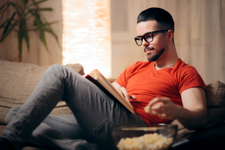 Man Relaxing at Home Reading a Book Imagens
