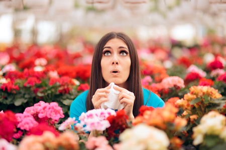 Woman Surrounded by Flowers Suffering from Allergies Stock Photo