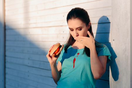 Clumsy Woman Staining Her Shirt with Ketchup Sauce Stockfoto