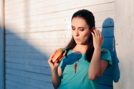 Femme maladroite tachant sa chemise avec de la sauce ketchup Banque d'images