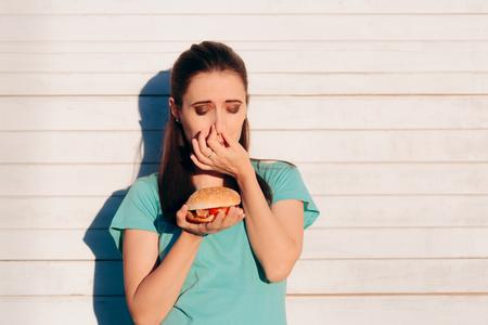 Vrouw met een stinkende en walgelijke hamburger Stockfoto