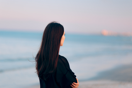 Sad Depressed Woman at the Seaside in Summer Sunset Stock Photo