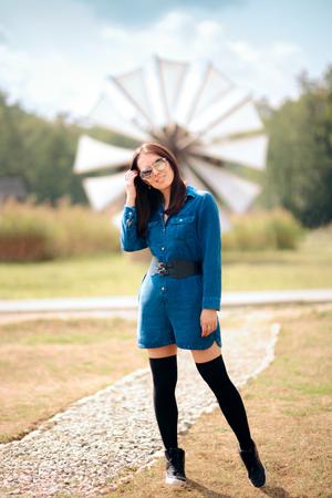 Trendige Touristin steht vor Windmühle Standard-Bild