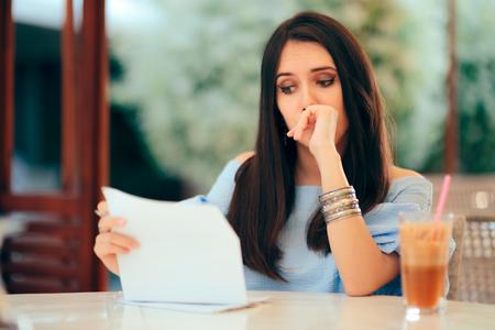 Besorgte Frau liest Dokumentenpapiere in einem Restaurant Standard-Bild
