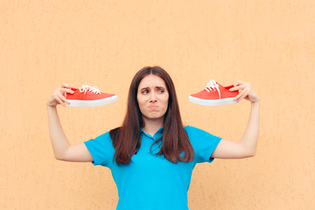 Unhappy Woman Holding a Pair of Red Sport Shoes