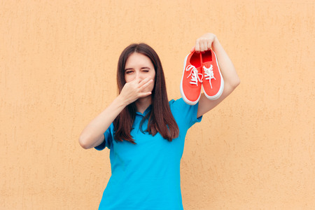 Woman Covering Nose Holding a Pair of Stinky Shoes