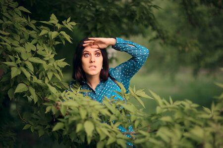 Mujer celosa curiosa espiando desde los arbustos