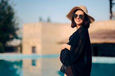 Pregnant Woman Relaxing on Vacation By The Pool 写真素材