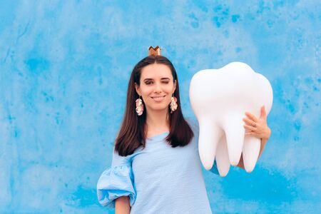 Woman in Tooth Fairy Costume Holding Big Molar Stock Photo - 129444945