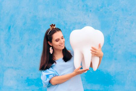 Woman in Tooth Fairy Costume Holding Big Molar Stock Photo