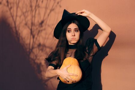 Halloween Woman in Witch Costume Holding Pumpkin
