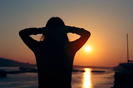 Hopeful Woman Looking at the Sunset by the Sea