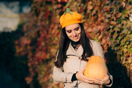 Autumn Woman Wearing Trench Coat Holding Pumpkin 写真素材