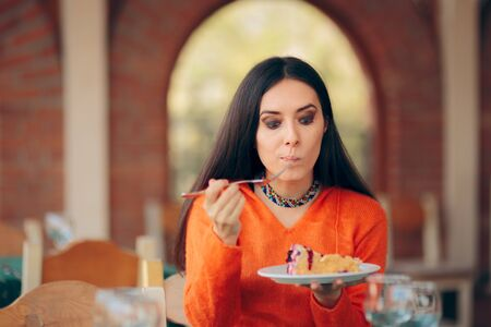 Funny Woman Eating Cake in a Restaurant 写真素材