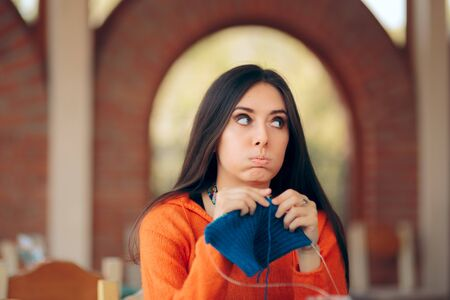 Woman Sitting at Table Knitting a Sweater
