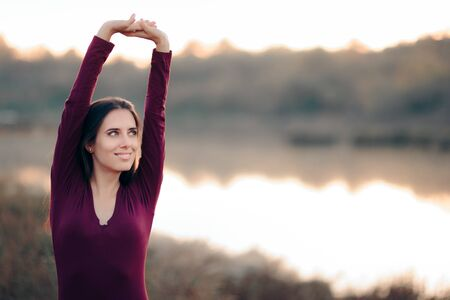 Woman Stretching Arms in By The Lake Banque d'images