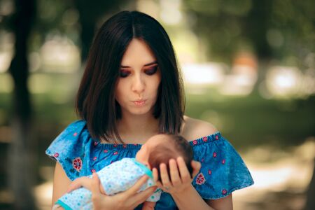 Happy Mother Holding Newborn Baby in Outdoor Portrait