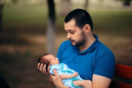 Portrait of a Happy Father Holding Newborn Baby