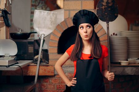 Female Chef in front of Pizza Oven Holding Peels