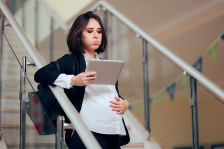 Pregnant Businesswoman with PC Tablet Felling Baby Kicking